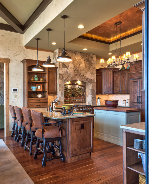 rustic kitchen with stained wood cabinets, wood floors, large natural stone accent wall and matching rustic decor