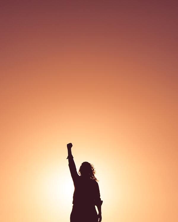 Uma mulher com o braço direito levanto em um punho fechado.