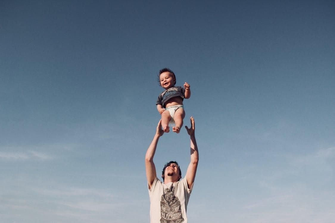 Фотография мужчины, воспитывающего ребенка под голубым небом