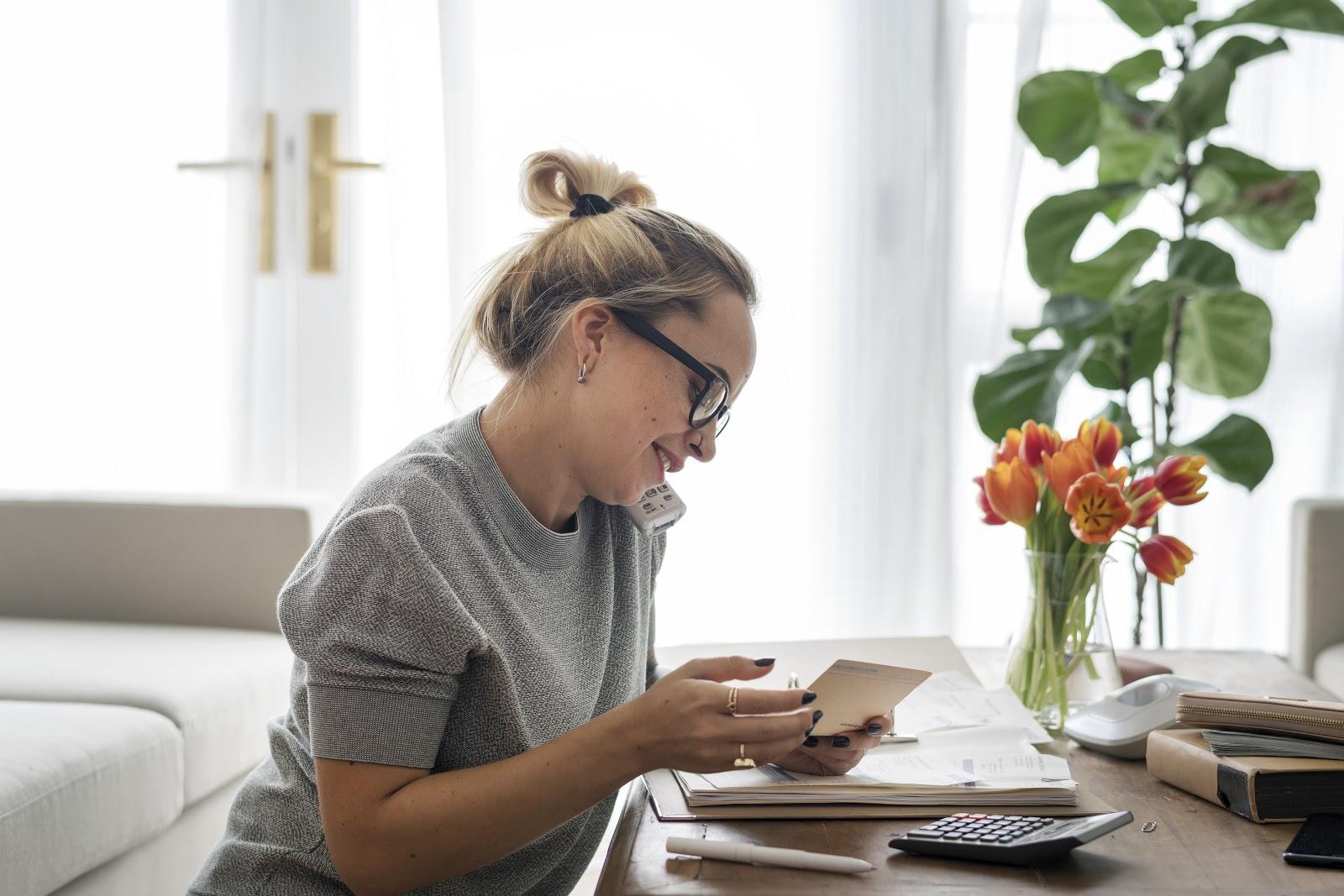 Mulher trabalhando em sua casa, no telefone e vendo suas notas fiscais para solicitar o reembolso da empresa.