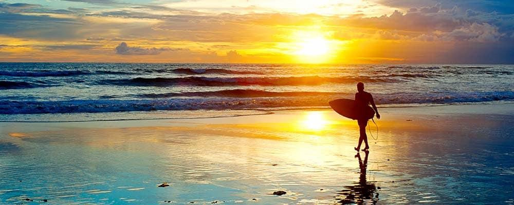 Surfer on beach in front of sunset