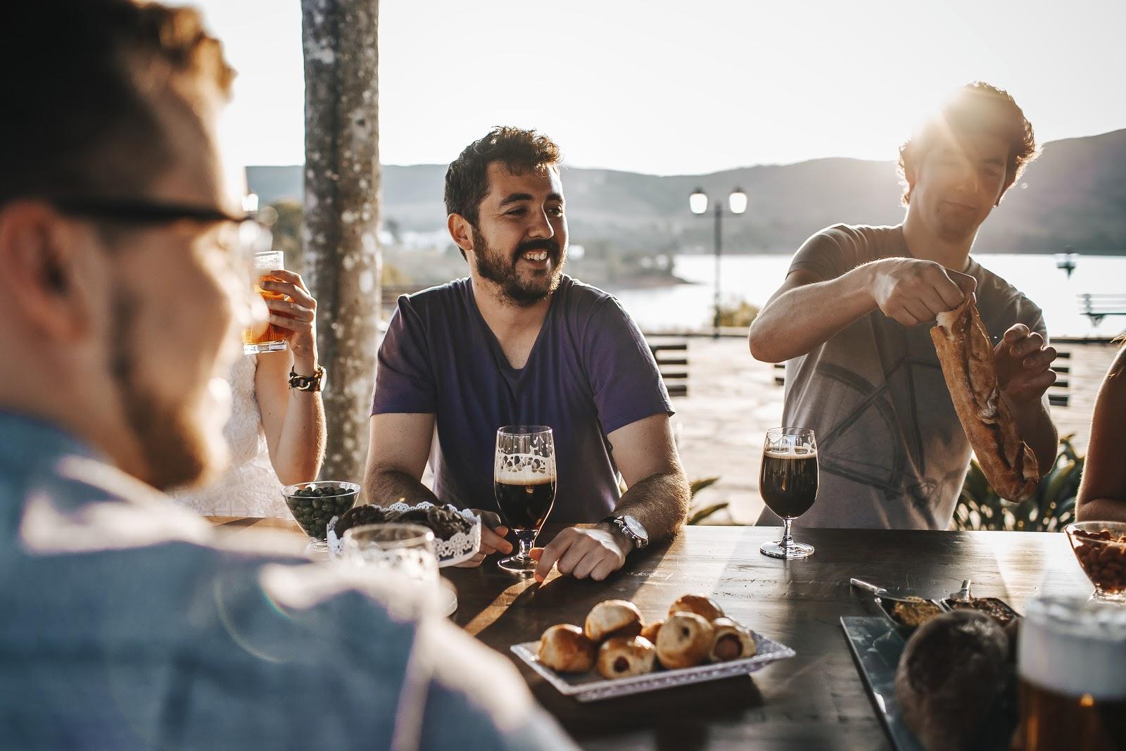 Homens em um momento de descontração, em uma confraternização corporativa externa, com drinks e snacks