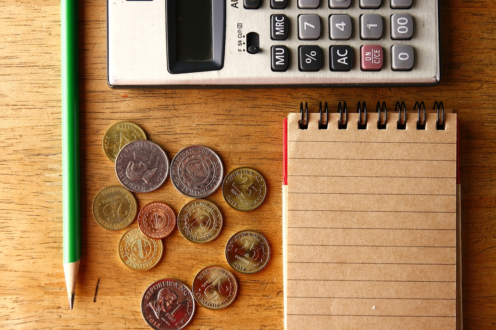 Coins, pencil, notebook, and calculator