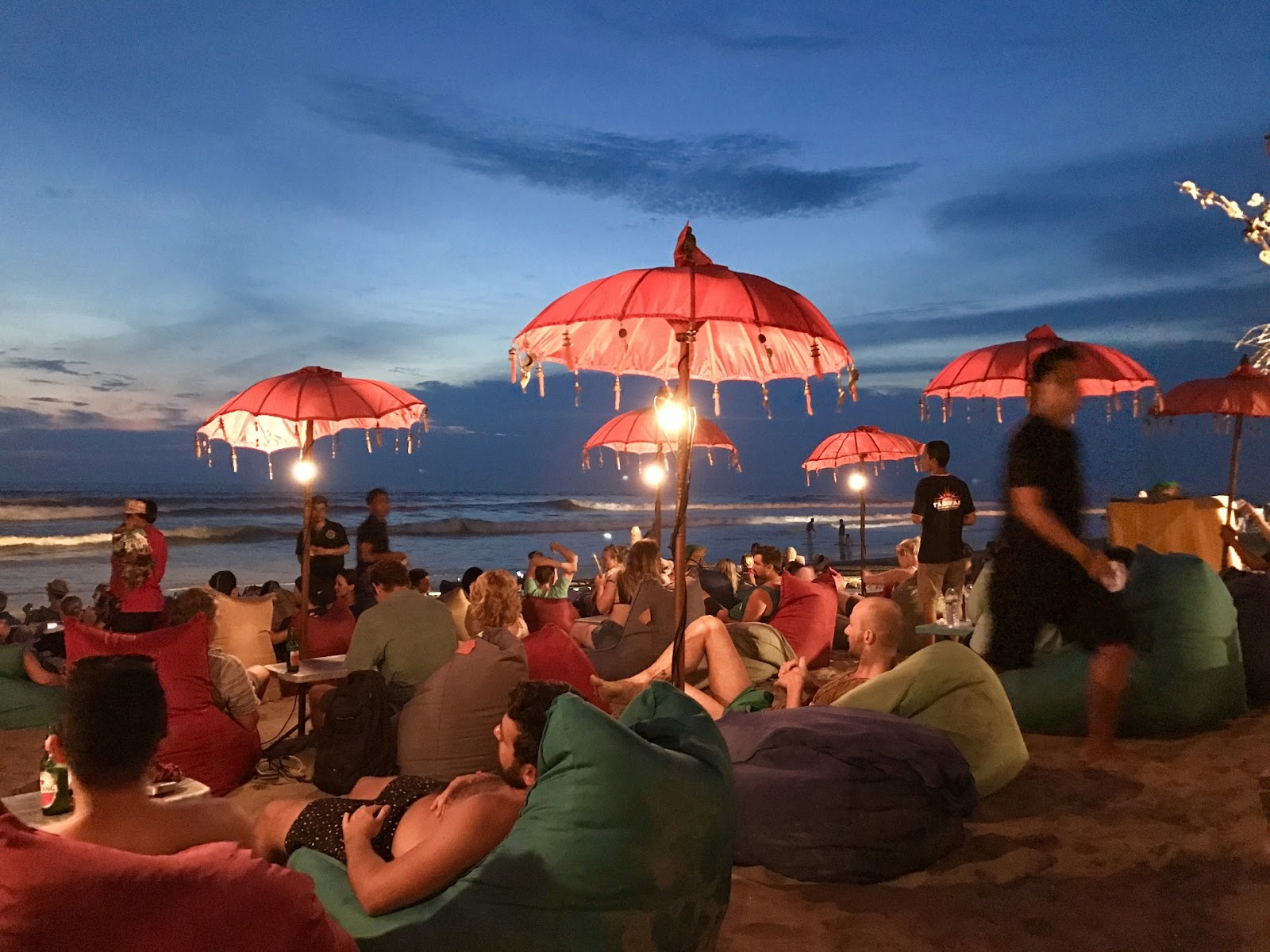 أشخاص يجلسون على الشاطئ لمشاهدة غروب الشمس