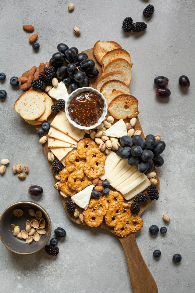 a wooden cheese board with pretzels, crostini, grapes, nuts, and fig jam on top