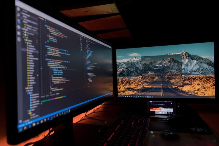 Dois computadores ligados em telas com pastas.