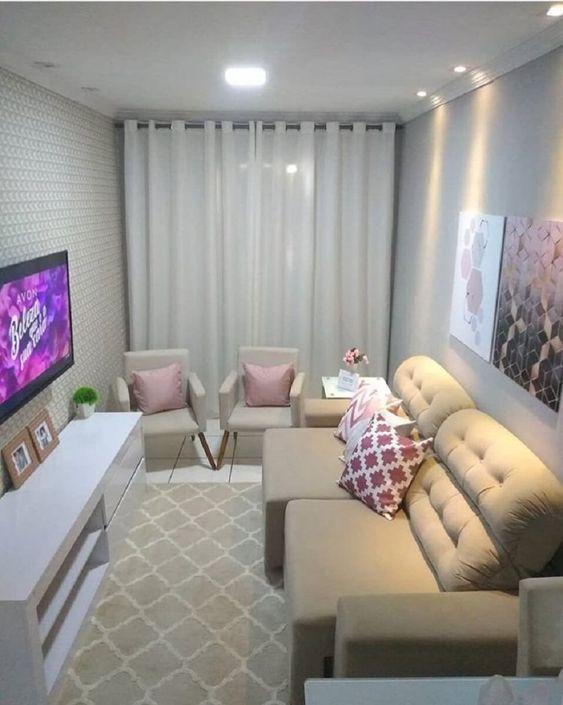 Ambiente de sala clássico, com cores claras, sofás e poltronas creme, almofadas rosas e bancas, quadros decorativos e rack branca.