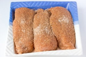 Куриные грудки хорошо моем под холодной проточной водой, просушиваем бумажным полотенцем, тщательно натираем пряной смесью. Выкладываем грудки в миску, накрываем пищевой плёнкой и отправляем в холодильник на 24 часа. За это время мясо пустит сок, его сливать не нужно, пусть оно так и стоит — маринуется.