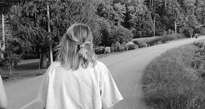 A photo of Molly walking down the road. There are trees on either side, the frame of her hair is tied back in a low twist. She's wearing a white t-shirt.