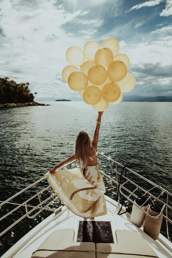foto de uma mulher no barco segurando balões