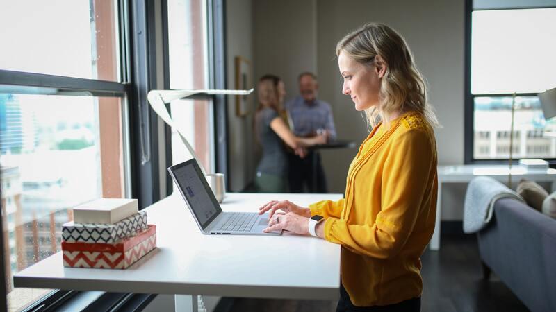 Femme qui travaille dans un espace de travail avec un bureau debout