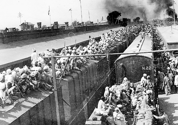 Refugees crowded onto the tops of train cars while fleeing during the Partition.