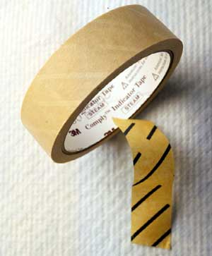 Roll of sterilization tape with tape piece showing color change after autoclaving.