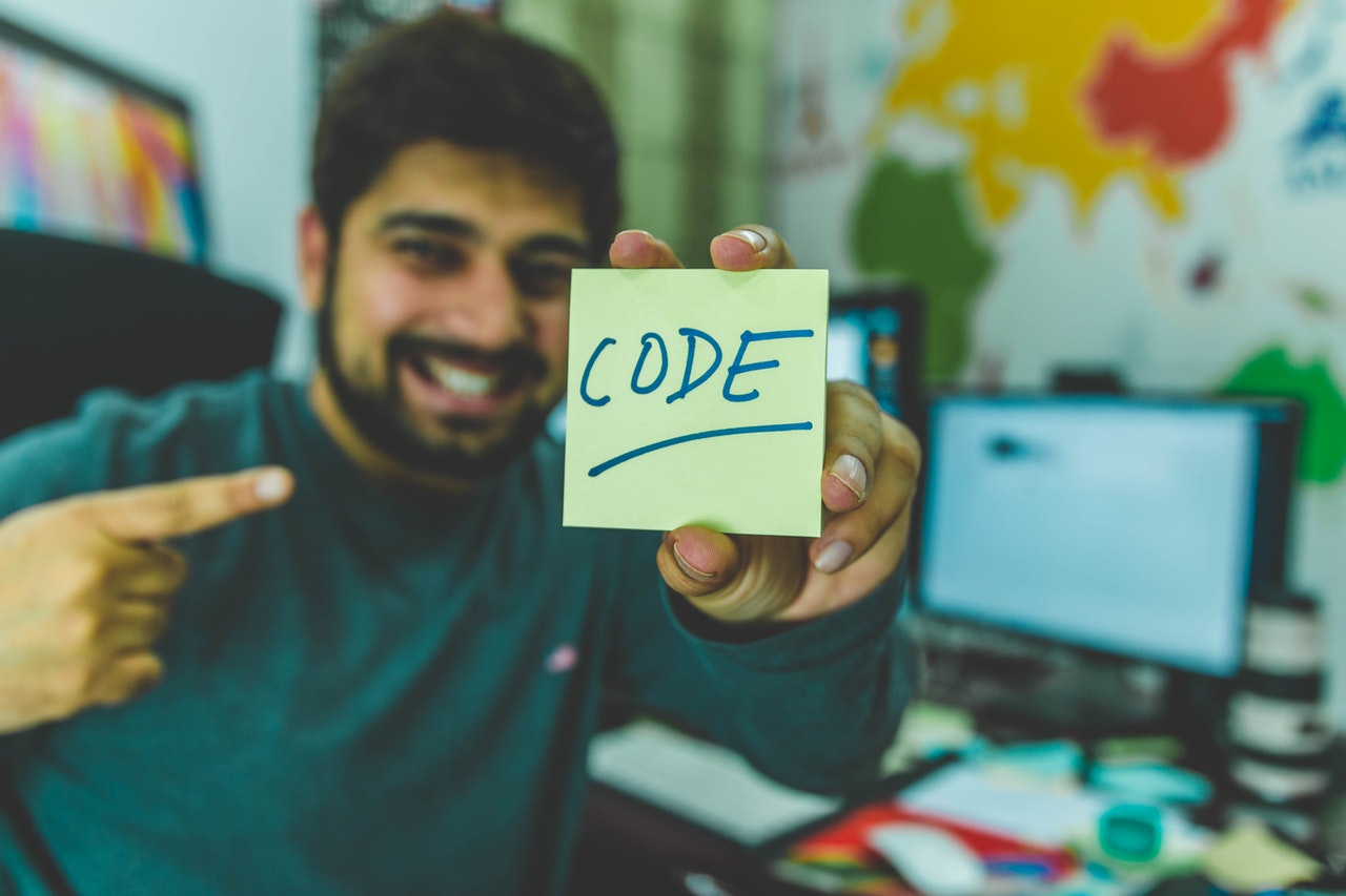 "Man in a sweater holding a yellow sticky note with ""code"" written on it"