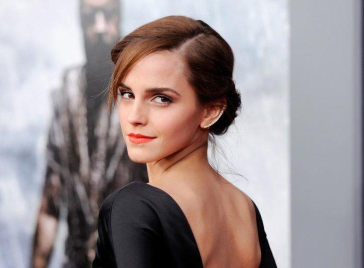 Emma Watson de espaldas, girando de perfil mostrando su vestido negro
