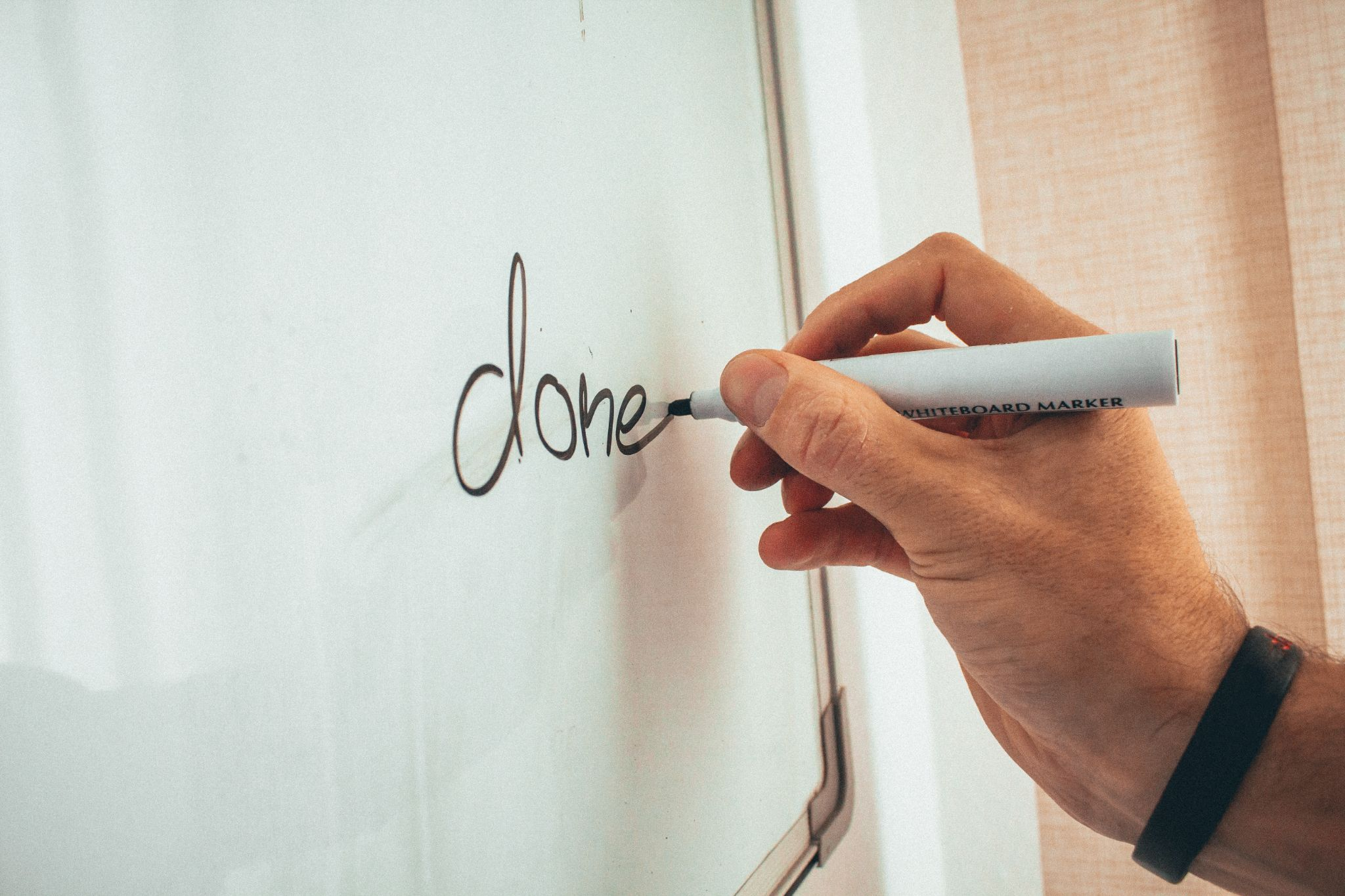 a hand writing the word 'done' on a whiteboard.