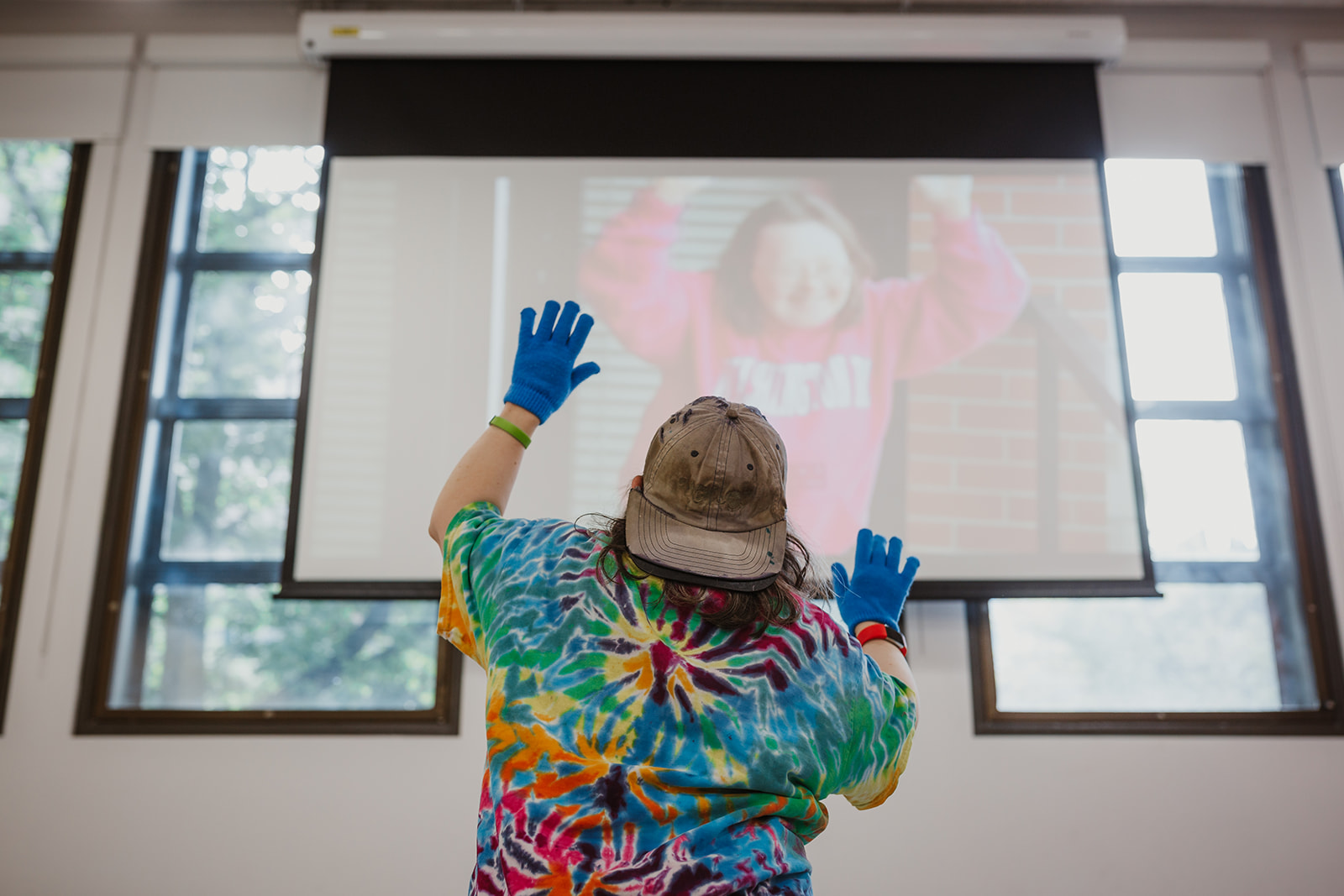 On July 22, 2019, Teresa raises her hands and dances, mimicking the screen image of herself in a Change.org video from 2014. Photo by Isabella Sarmiento, This Is It Studios.