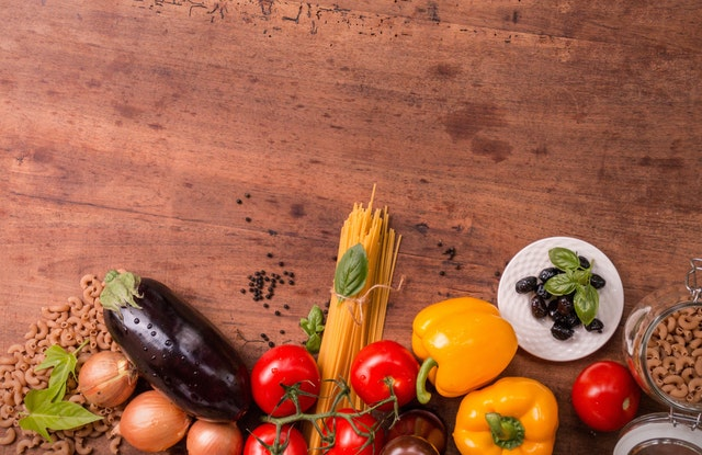 row of fruits, vegetables and grains on a counter top