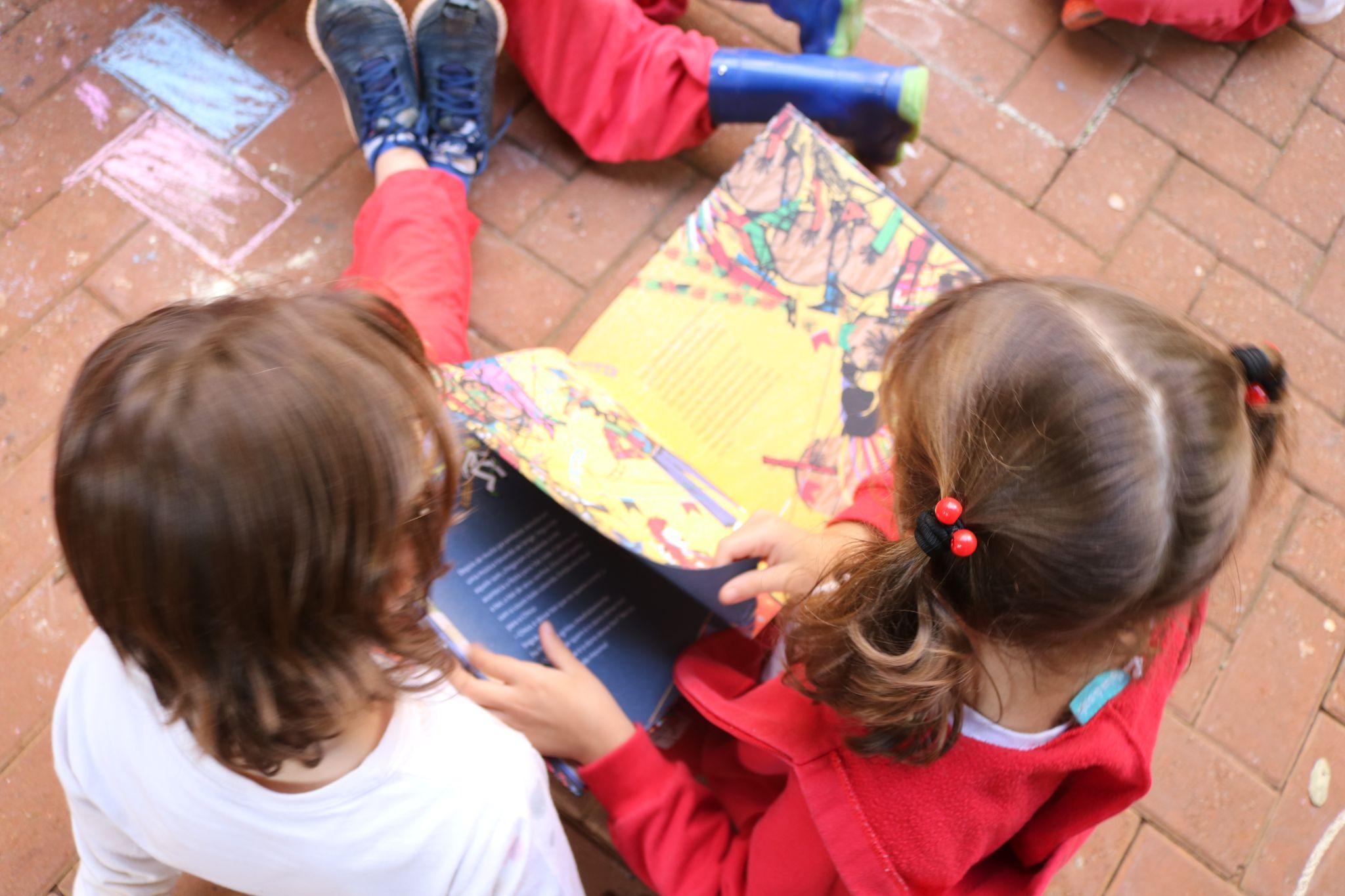 A imagem mostra duas crianças lendo um livro.