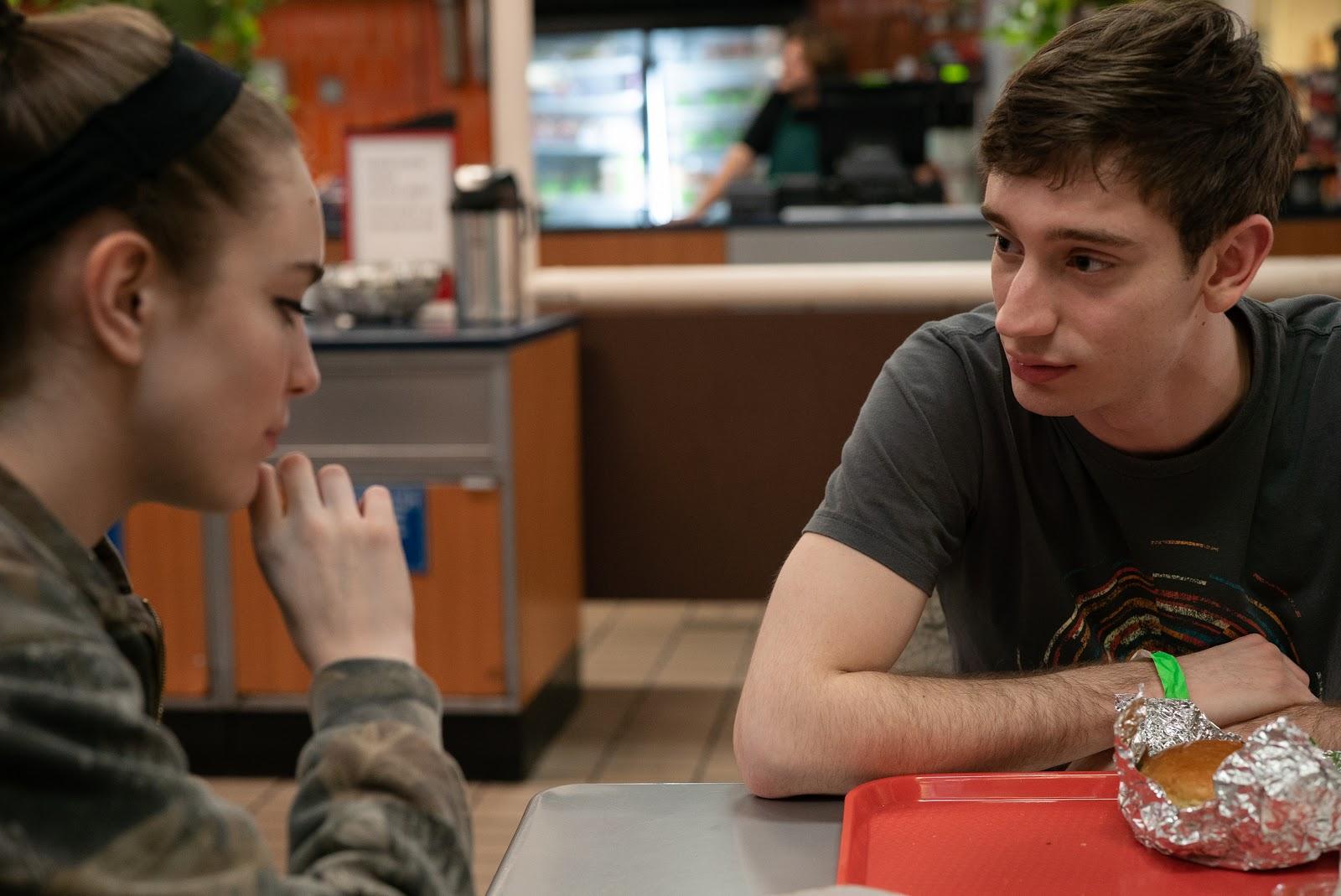 Jasper talks to Skylar across a table at a fast food restaurant.