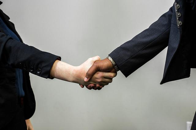 handshake between professionals who help outsource your business needs