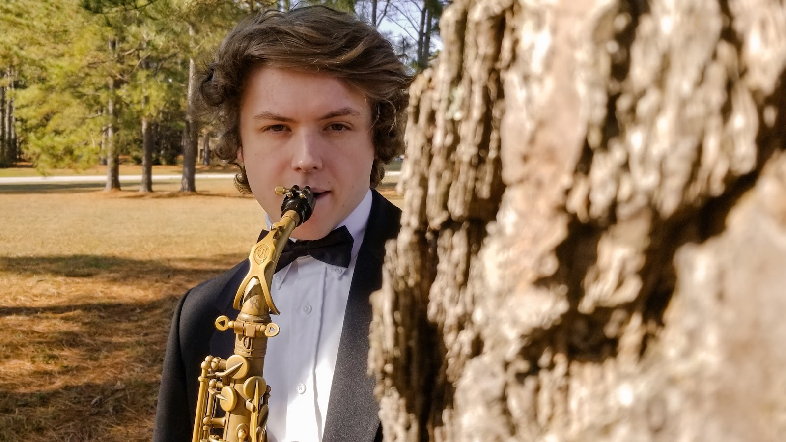 Peter Bailer stands outside behind a large tree while playing the saxophone.