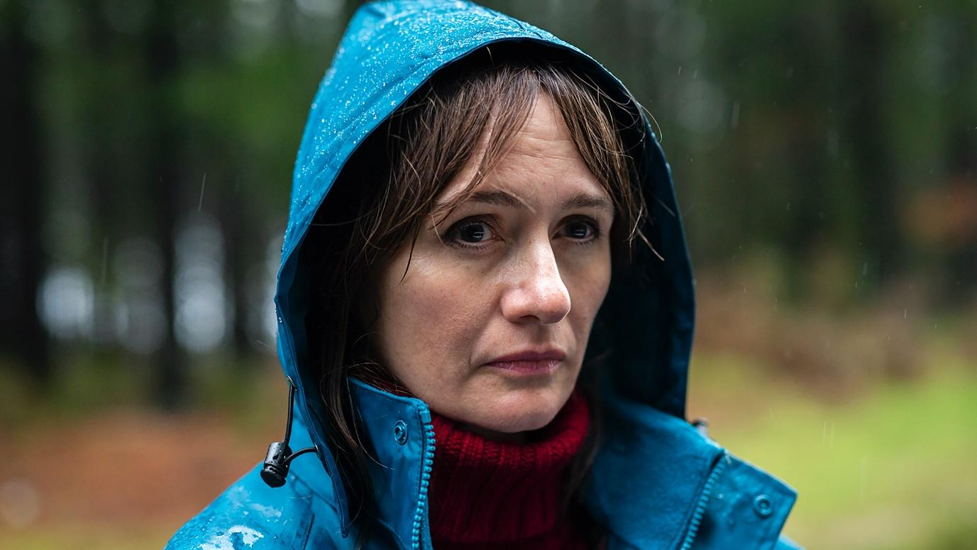 Emily Mortimer as Kay in Relic. She wears a bright blue raincoat with the hood up.