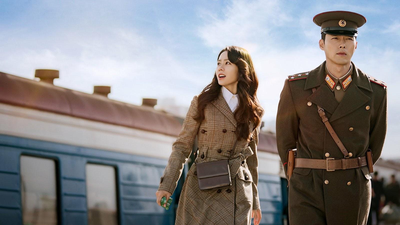 Imagem exibindo os protagonistas com um trem em segundo plano. Em primeiro plano, no centro, uma mulher sul-coreana olha o horizonte. À sua direita, um militar norte-coreano fardado olha para a frente.