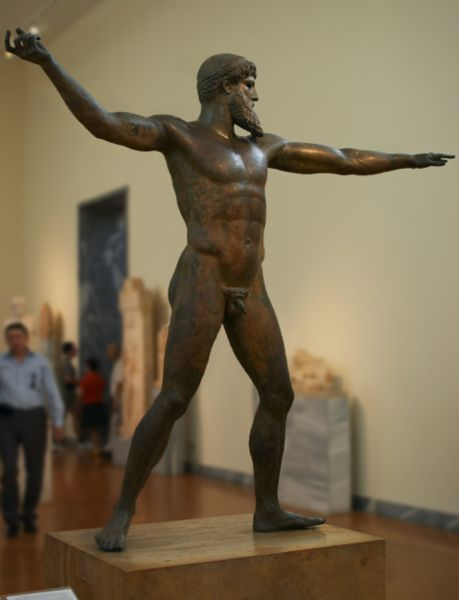 Bronze statue of an athletic nude male with a beard with his right arm in position to hurl a thunderbolt or a trident.