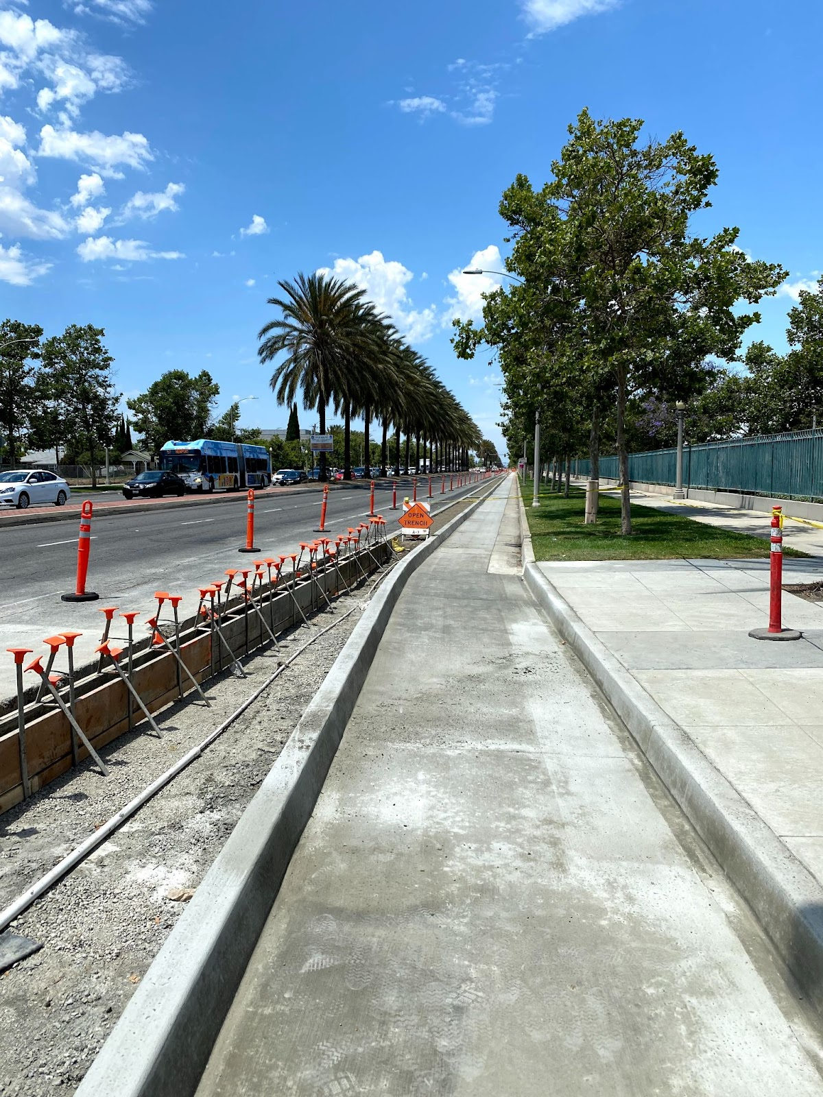 An image of the construction of the Bristol St Bike Lane. Shows a lovely blue sky, a row of palm trees, and the protected bike lane in construction. There are little orange headed thingies sticking up out of the ground on the left side of the image, possible to support the concrete being put in for the median divider to protect the bikes from the cars.