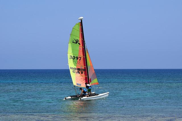 Two sailors ready their personal watercraft sailing catamaran.
