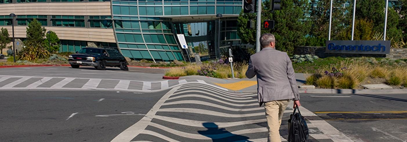 Image of a man using a pedestrian crossing where the lines of the crossing appear to be wavy
