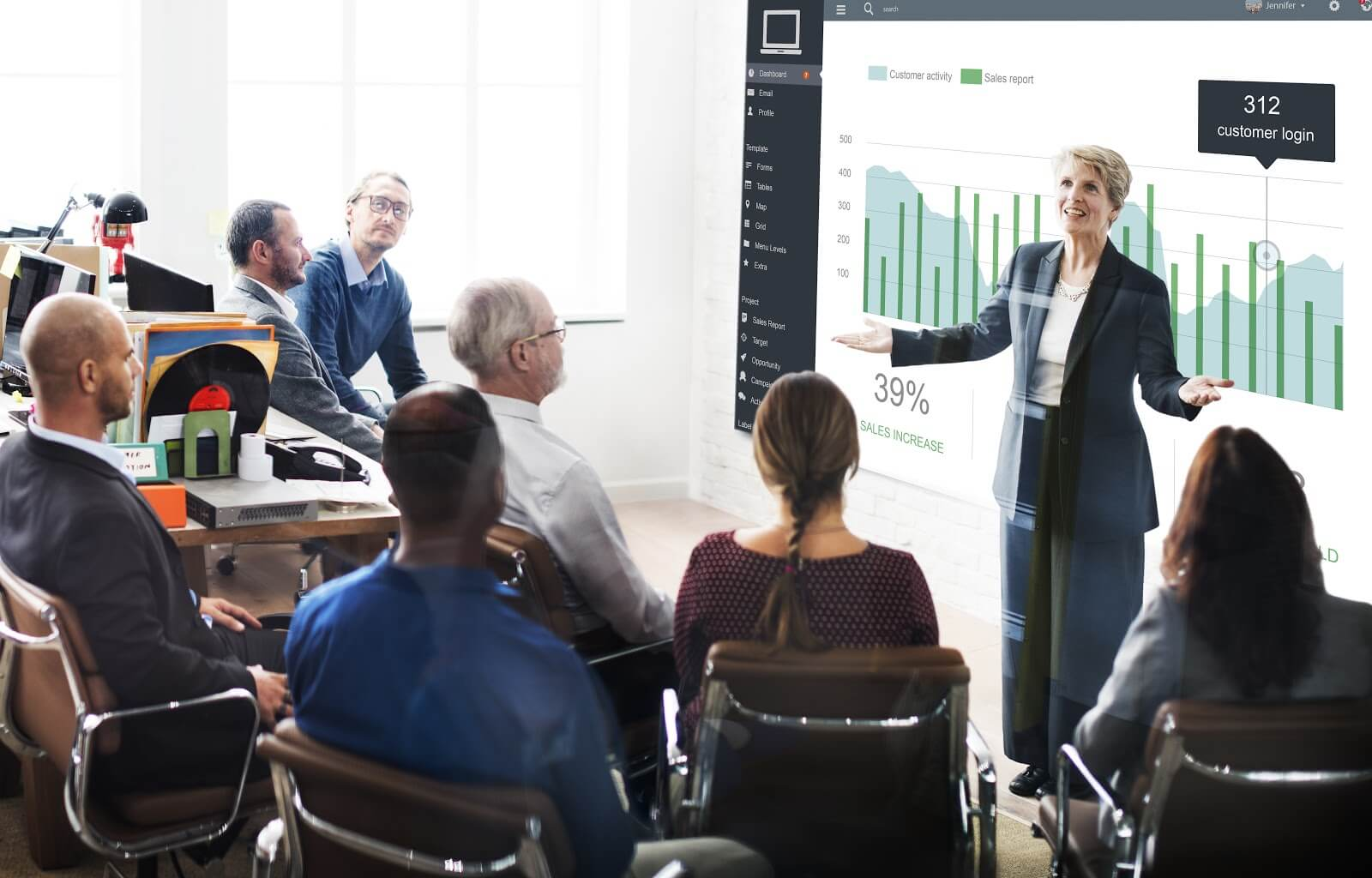 Older professional woman presenting data to room of colleagues