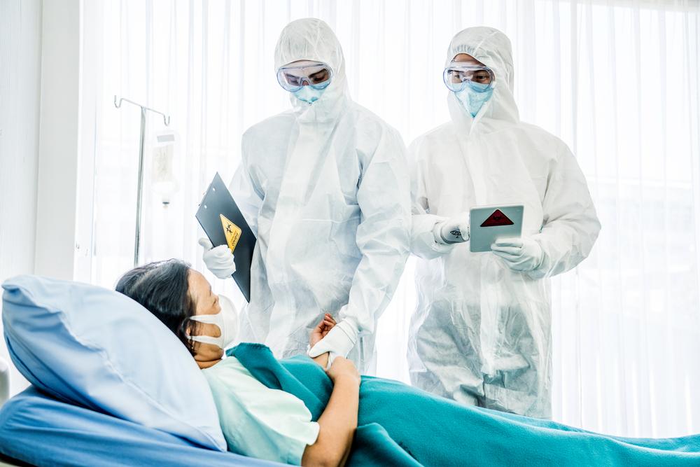 Médicos com equipamento de proteção individual tratando senhora com máscara
