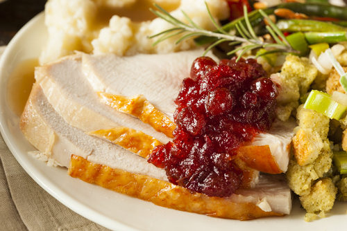 a plate of Thanksgiving dinner including turkey, cranberry sauce, mashed potatoes and gravy, and stuffing