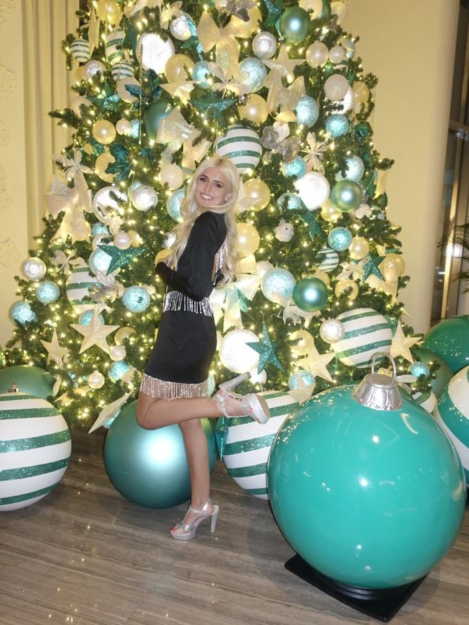 A person posing in front of a christmas tree  Description automatically generated with medium confidence