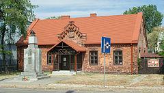 """Budynek """"Murowanki"""" w Wawrze, a przed nimpomnik poświęcony Piłsudskiemu ibohaterom Wawra 1918-1920"""
