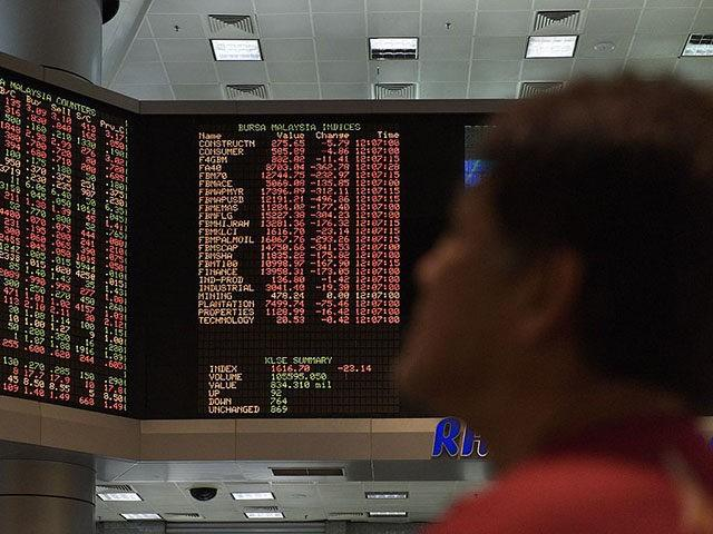A trader watches electronic boards showing stock movements at the Malaysia Stock Exchange in Kuala Lumpur on June 24, 2016.
