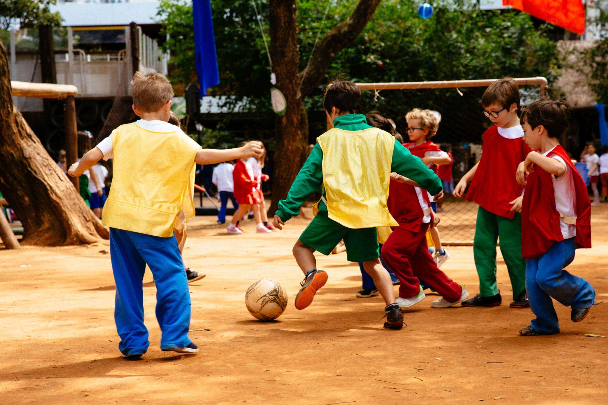 A imagem mostra um grupo de crianças jogando futebol em um quintal com chão de terra.