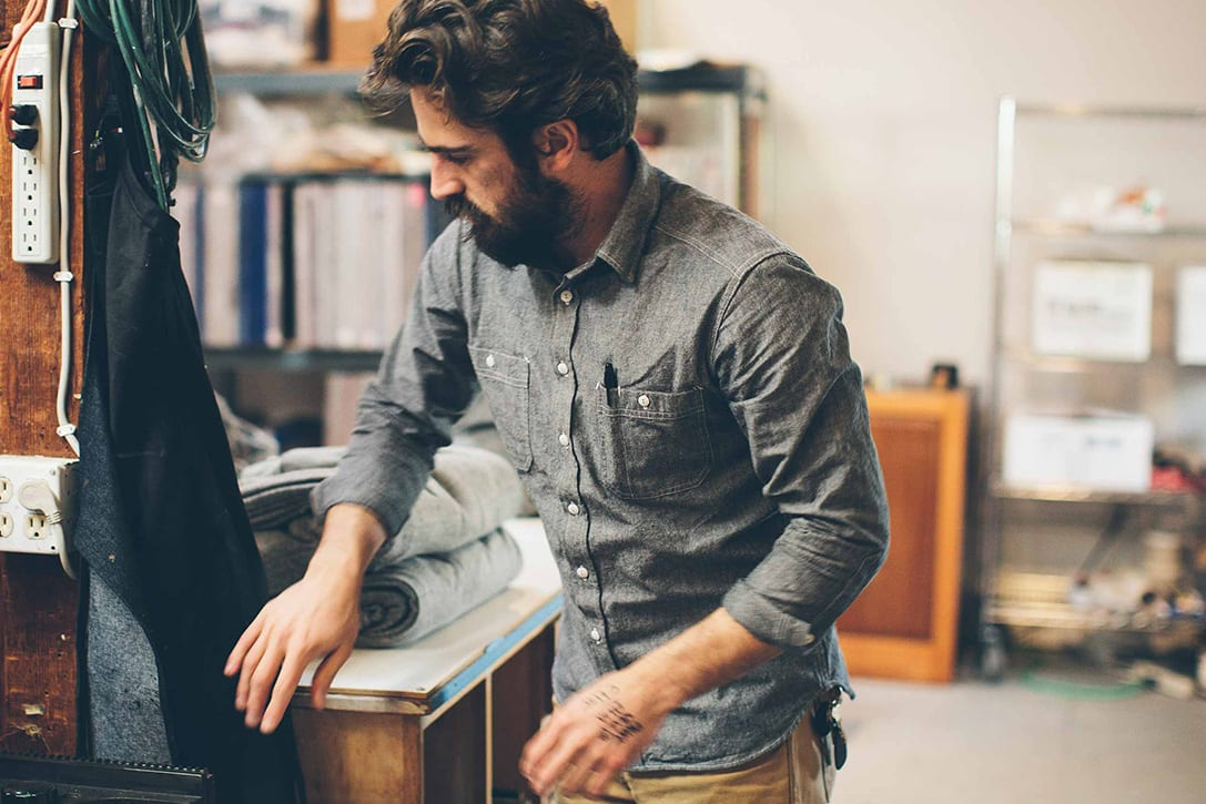 A man working in a work station while wearing a chambray shirt