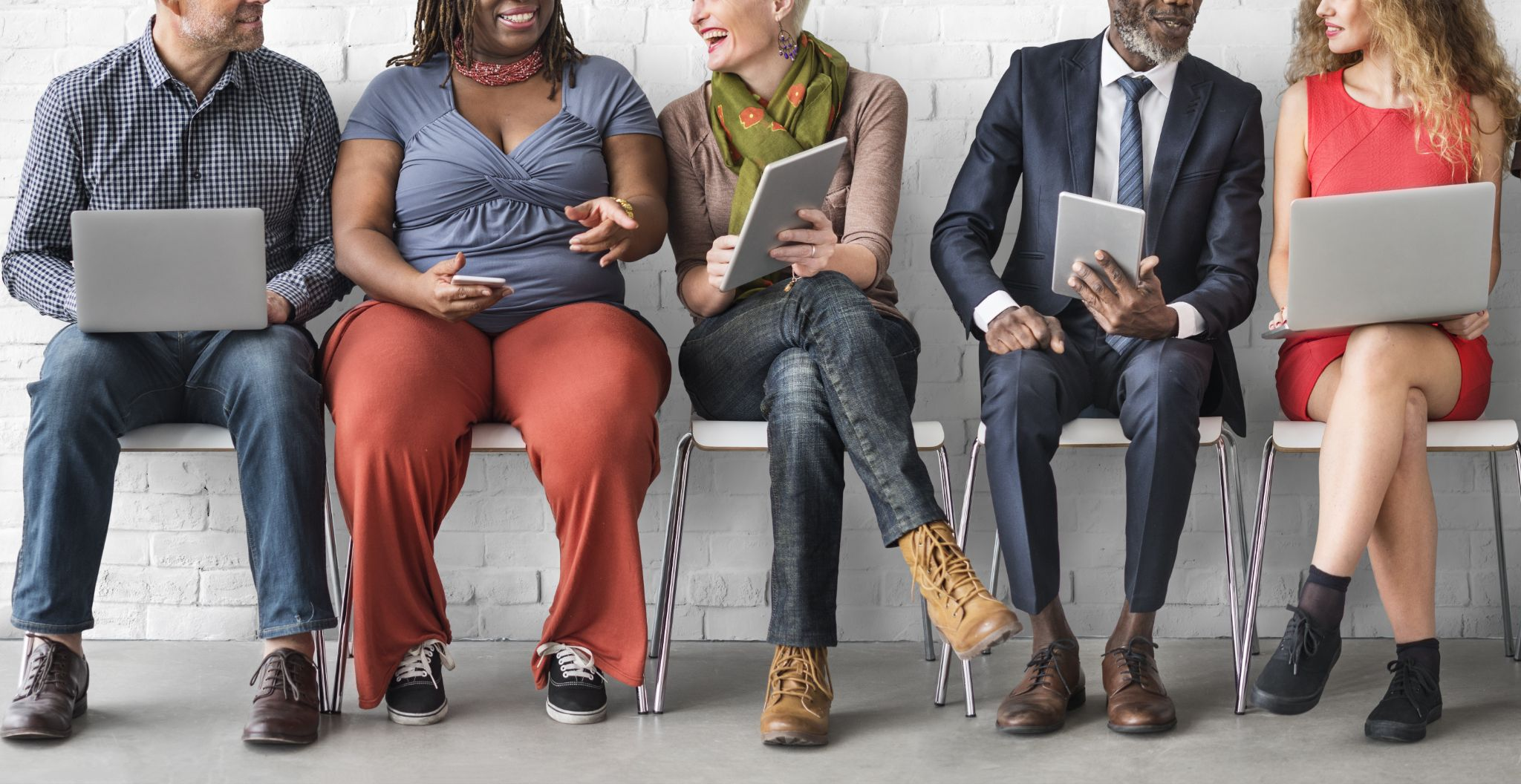 Group of diverse people sitting on chair looking at different devices in their hands