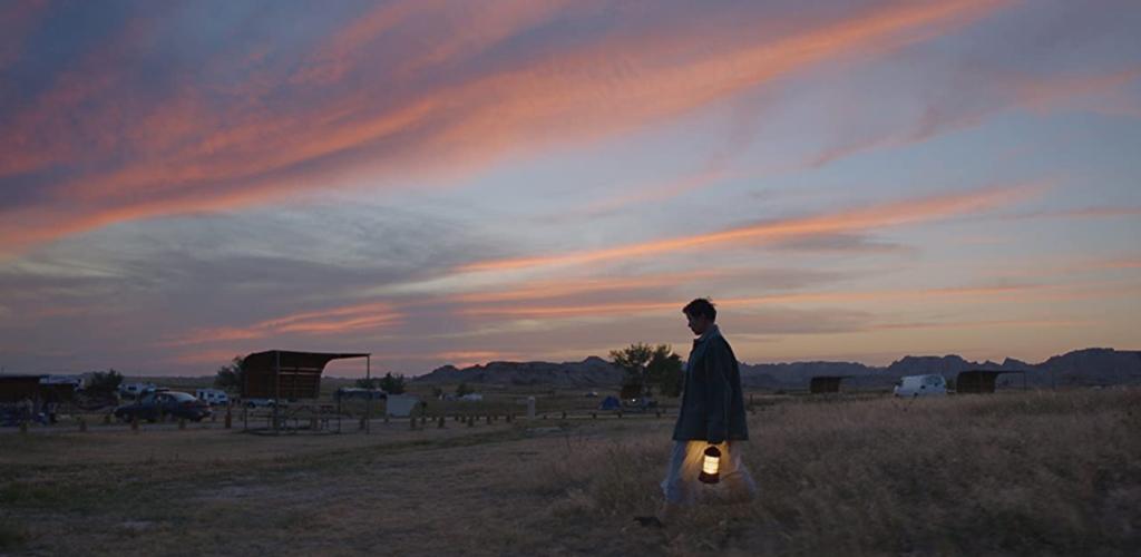 Personagem anda em campo vasto durante o entardecer. Ele segura uma lamparina nas mãos. O rapaz é jovem e ao seu redor, existe um ponto de espera de ônibus e carro. É dirigido por Chloé Zhao, uma das mulheres que receberam prêmios no Oscar 2021.