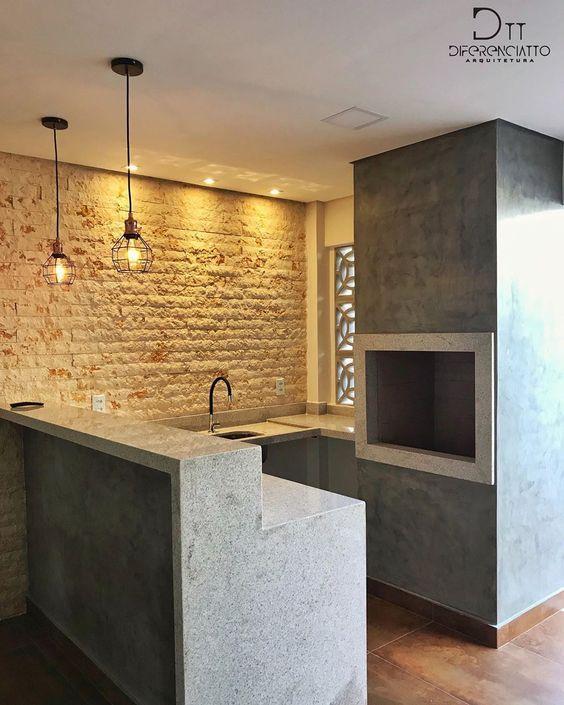 Área em estilo industrial com churrasqueira e bancada revestidas de pedra natural, paredes com revestimento de pedras, piso amadeirado, cobogó e lâmpadas pendentes.