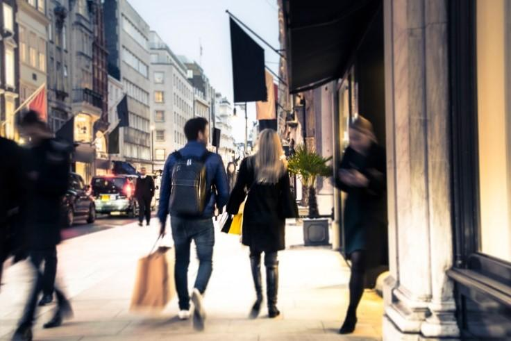 A couple carrying shopping bags walk in front of shops on Oxford Street