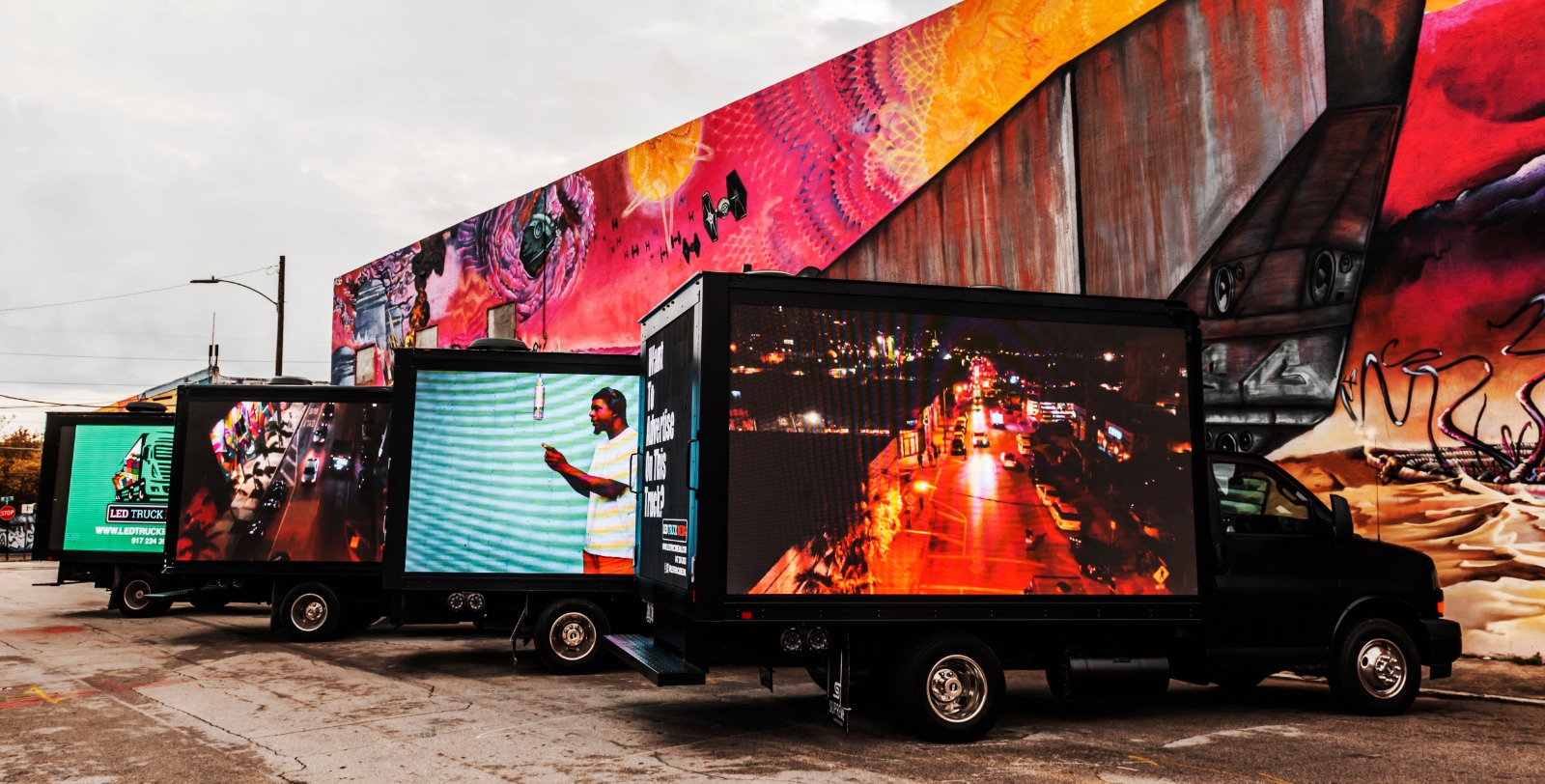 trucks lined up with digital ads on the sides of the trailers