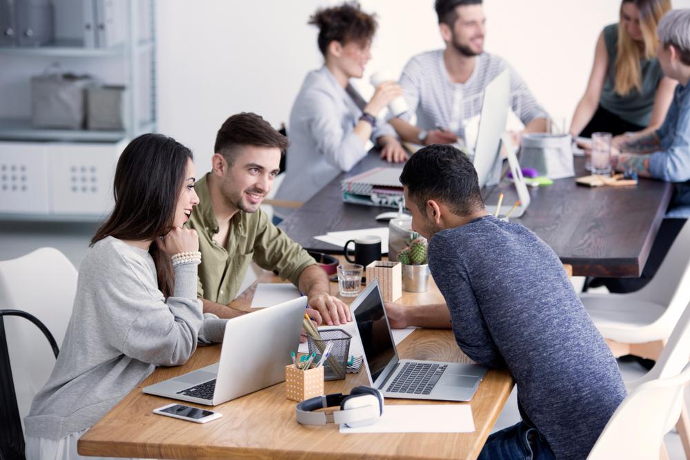 Três pessoas conversando em uma mesa de escritório.
