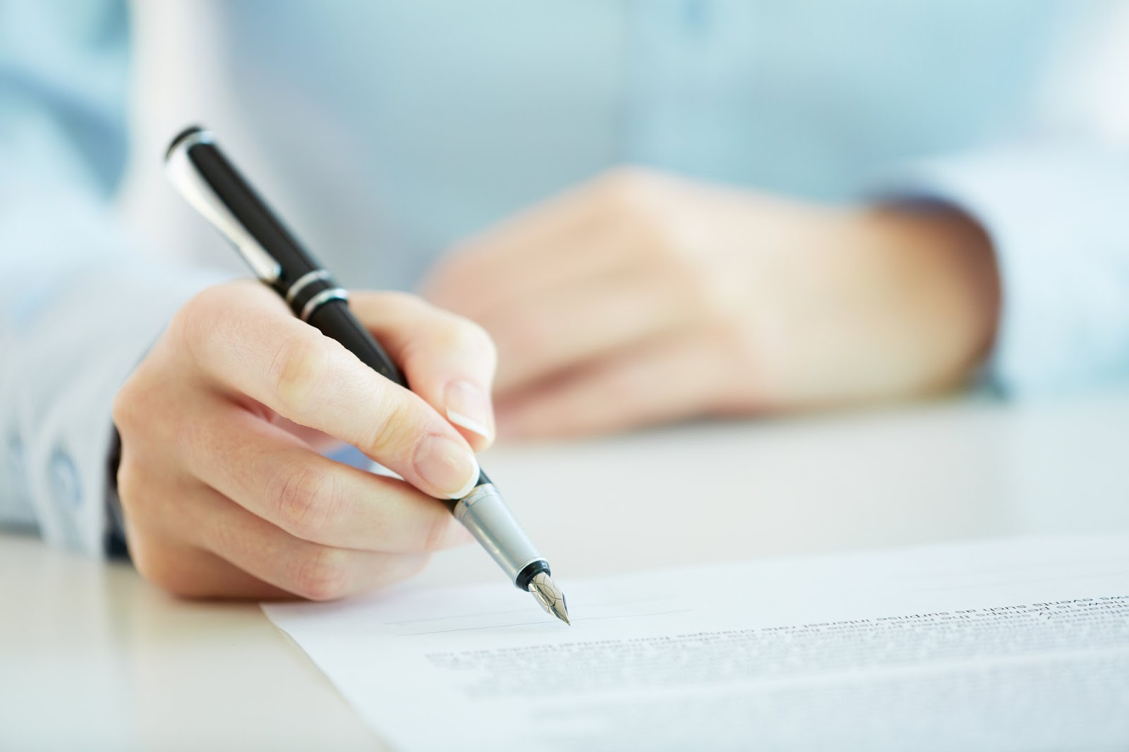 A hand holding a pen on typed document