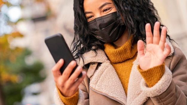 Woman wearing a medical mask while having a video call on her smartphone