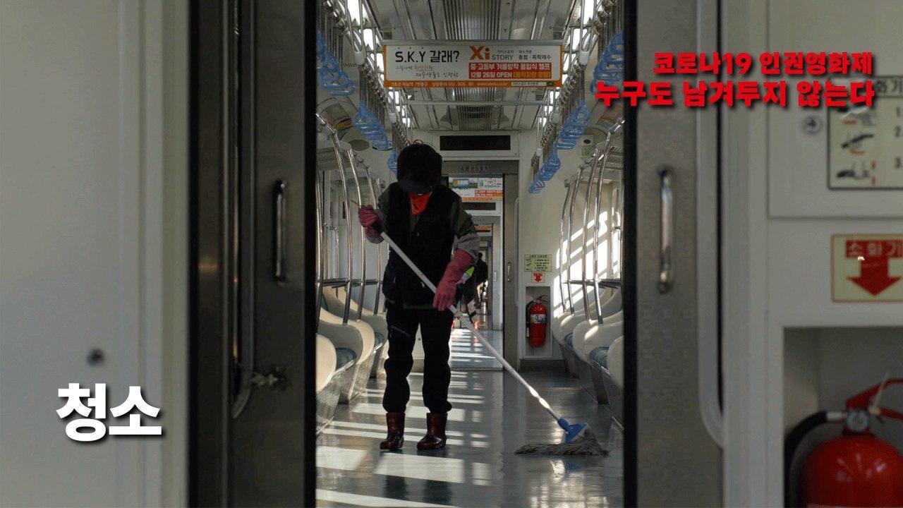 사진4. 영화 청소의 스틸컷. 텅 빈 지하철 안.고무장갑을 끼고 빛을 가리는 모자를 쓴 청소노동자들이 대걸래로 청소하고 있다.