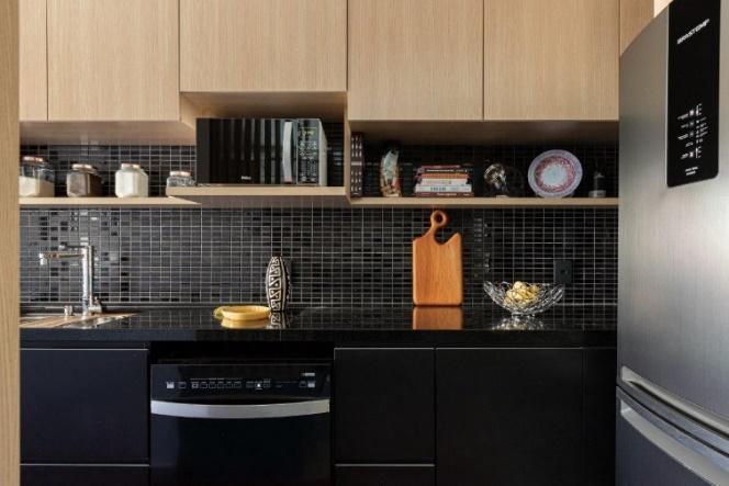 Cozinha com armário inferior e bancada preta, armário superior amadeirado, pastilhas pretas e geladeira de inox.
